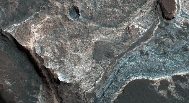 This image from NASA's Mars Reconnaissance Orbiter (MRO) shows the western wall of a small pit that is located along the floor of a larger trough in Coprates Catena. Dark layers line the bottom; light-toned layers are near the top.