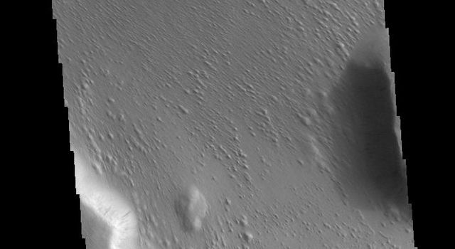 This image captured by NASA's 2001 Mars Odyssey spacecraft is located in Medusae Fossae. Along the cliffside several dark streaks are visible.