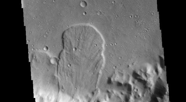 This image captured by NASA's 2001 Mars Odyssey spacecraft is located in an unnamed crater within Tyrrhena Terra. The 'mitten' shaped feature extends from the crater rim (bottom of frame) onto the crater floor.
