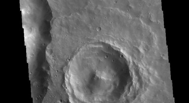 This image captured by NASA's 2001 Mars Odyssey spacecraft shows several craters. The interior of the central one has retained much of the original topography, including the central peak.