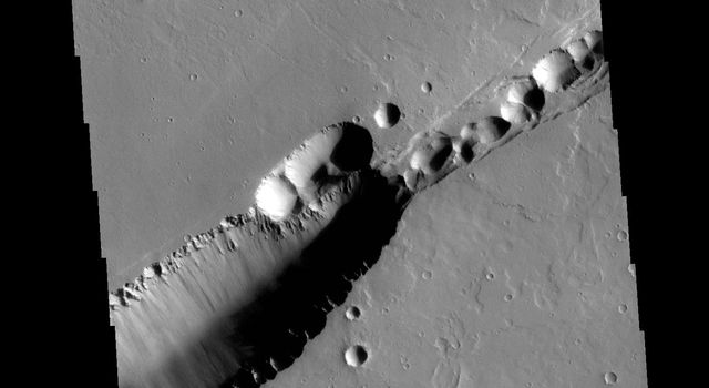 The feature that crosses this image captured by NASA's 2001 Mars Odyssey spacecraft is a graben. Graben are formed by tectonic action, where a block of material moves downward between a pair of faults.