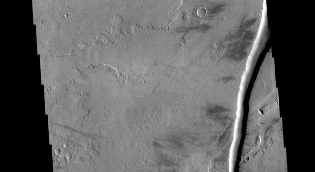 The linear channel in the bottom half of this image from NASA's 2001 Mars Odyssey spacecraft is part of Olympica Fossae. Olympica Fossae is a complex channel form located on the Tharsis plains between Alba Mons and Olympus Mons.