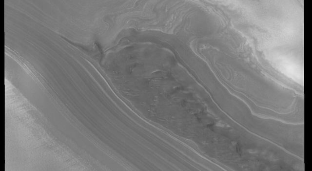 This image from NASA's 2001 Mars Odyssey spacecraft shows part of the margin of the north polar cap and the surrounding plains. The layering of the ice is easily visible due to the dust that is deposited on the top of the ice every year.