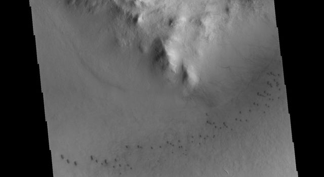 Milankovic Crater is located in central Arcadia Planitia. This image from NASA's 2001 Mars Odyssey spacecraft shows small sand dunes on the crater floor, and larger dunes within the central crater peak/pit feature.