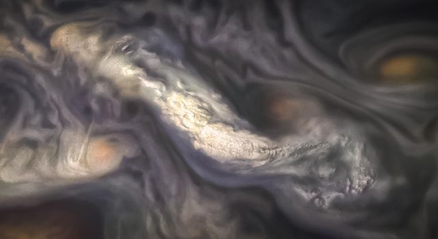 This image captures a high-altitude cloud formation surrounded by swirling patterns in the atmosphere of Jupiter's North North Temperate Belt region as seen by NASA's Juno spacecraft.