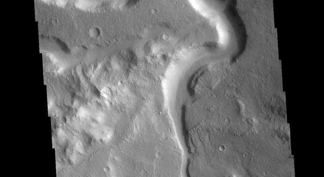 This image from NASA's Mars Odyssey shows an unnamed channel in Xanthe Terra. The large bend in the channel was created as the flow of liquid from the bottom of the image was deflected by a ridge that extends diagonally from the left center.