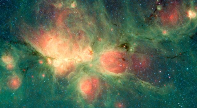 The Cats Paw Nebula, imaged here by NASAs Spitzer Space Telescope, is a star-forming region that lies inside the Milky Way Galaxy.