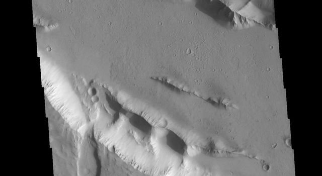 This image from NASA's Mars Odyssey shows part of one of the Elysium Fossae on the western flank of the Elysium volcanic complex. The fossae have both a tectonic and volcanic origin.