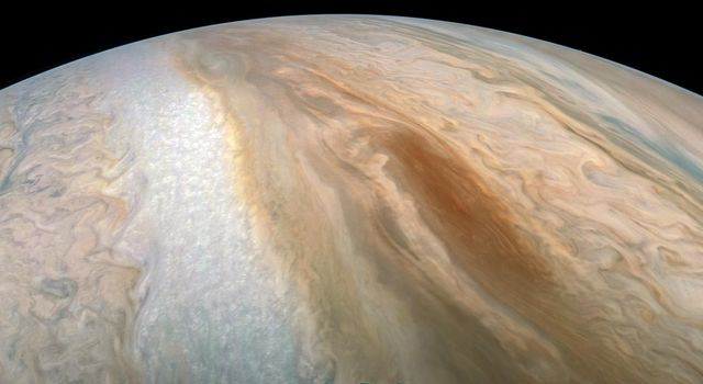 A long, brown oval known as a brown barge in Jupiter's South Equatorial Belt is captured in this color-enhanced image from NASA's Juno spacecraft.