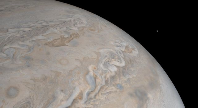 Jupiters moon Io rises just off the horizon of the gas giant planet in this image from NASAs Juno spacecraft.