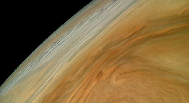 Colorful swirling clouds in Jupiters North Equatorial Belt practically fill this image from NASAs Juno spacecraft.