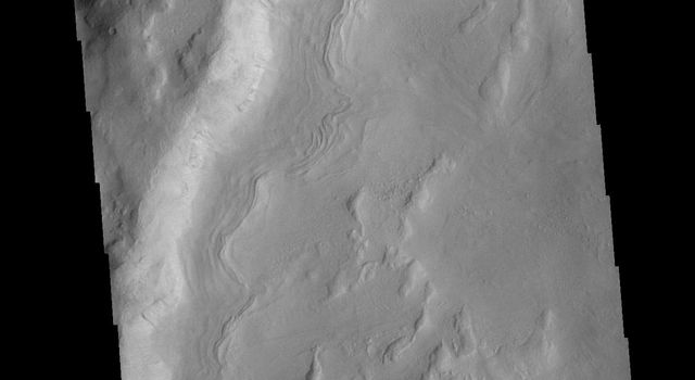 This image from NASAs Mars Odyssey shows an unnamed crater in Noachis Terra. The sinuous feature near the bottom of the crater rim appears to have been caused by down slope movement of materials.