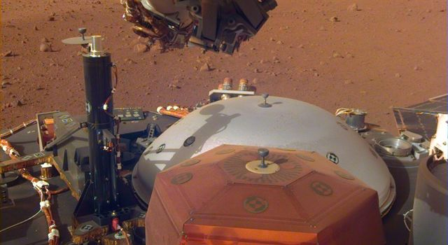 This image from InSights robotic-arm mounted Instrument Deployment Camera shows the instruments on the spacecrafts deck, with the Martian surface of Elysium Planitia in the background.