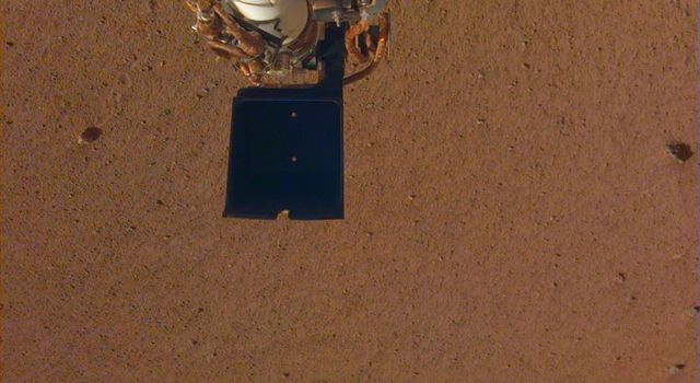 This image shows InSights robotic arm, with its scoop and stowed grapple, poised above the Martian soil.