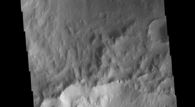 This image from NASAs Mars Odyssey shows a crater rim, which is shared by two craters.