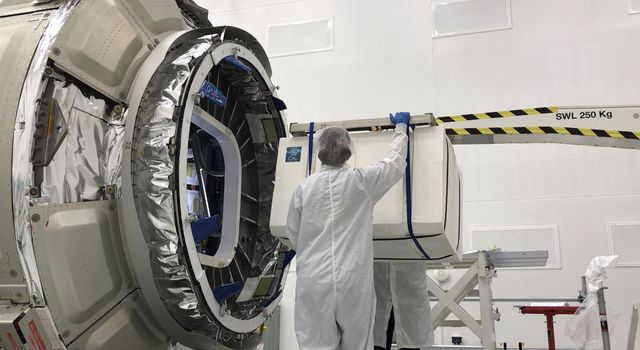 This image shows NASAs Cold Atom Laboratory, packaged in a protective layer, being loaded up onto a Northrop Grumman (formerly Orbital ATK) Cygnus spacecraft for its trip to the International Space Station.