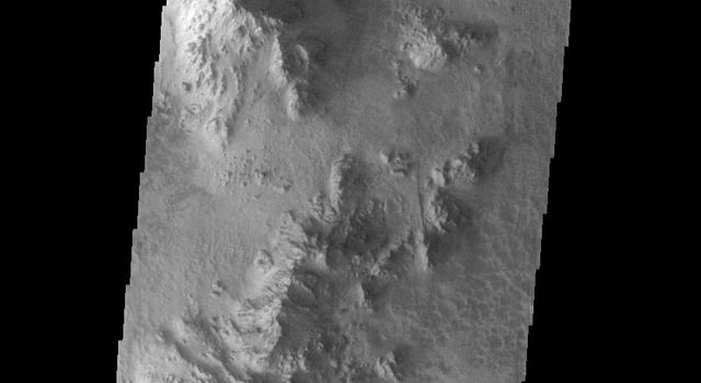 This image from NASAs Mars Odyssey shows part of the floor of Hale Crater and the elongate axis of the central peak mountains.