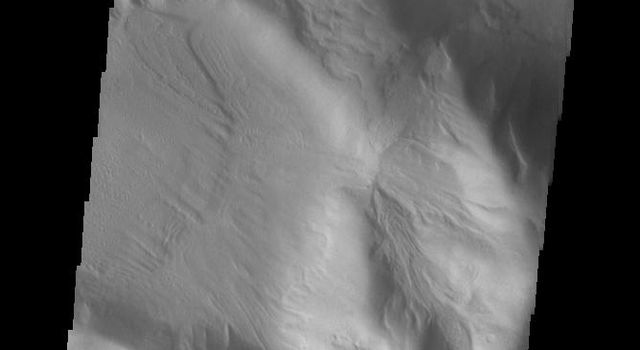 This image from NASAs Mars Odyssey shows an isolated mountain east of Hellas Planitia. Erosion is moving material down hill towards the lower elevations.