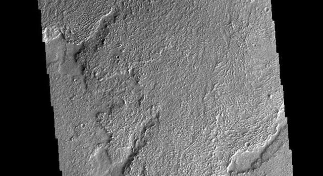 This image from NASAs Mars Odyssey shows a small part of Daedalia Planum. The lava flows originate from Arsia Mons, one of the large volcanoes in the Tharsis region.