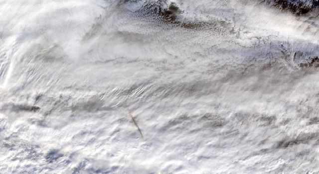 NASAs MODIS instrument, aboard the Terra satellite, captured this true-color image showing the remnants of a meteors passage, seen as a dark shadow cast on thick, white clouds on Dec. 18, 2018.