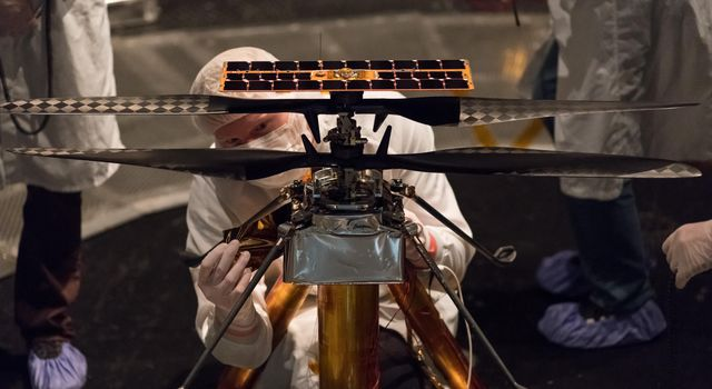 Members of the NASA Mars Helicopter team attach a thermal film to the exterior of the flight model of the Mars Helicopter. The image was taken on Feb. 1, 2019.