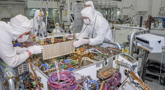 Engineers and technicians at NASAs Jet Propulsion Laboratory in Pasadena, California, integrate the rover motor controller assembly (RMCA) into the Mars 2020 rovers body.