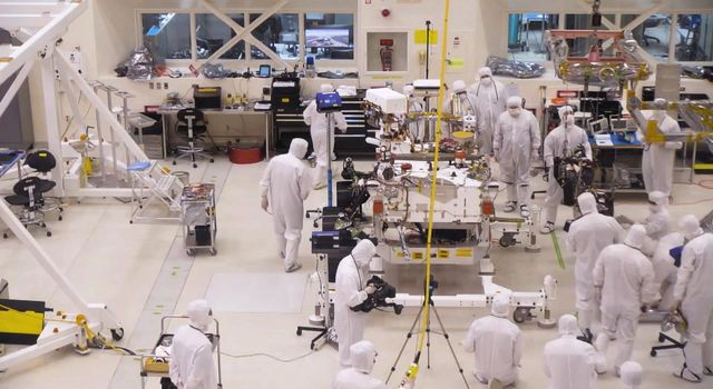 A team of engineers at NASAs Jet Propulsion Laboratory in Pasadena, California, install the legs and wheels on the Mars 2020 rover.