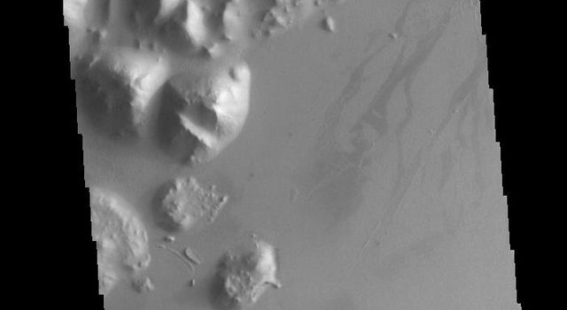 This image from NASAs Mars Odyssey shows two linear depressions which are part of Cerberus Fossae.