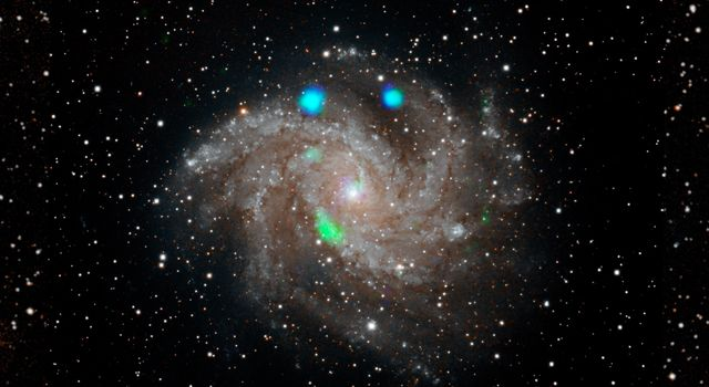 This visible-light image of the Fireworks galaxy (NGC 6946) comes from the Digital Sky Survey, and is overlaid with data from NASAs NuSTAR observatory (in blue and green).