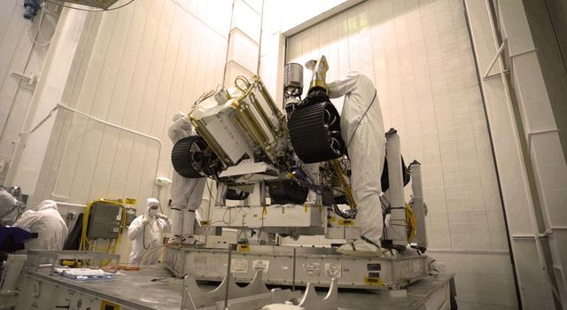 Engineers working on NASAs Mars 2020 mission remove the inner layer of protective antistatic foil from the rover after a move from JPLs Spacecraft Assembly Facility to the Simulator Building for testing.