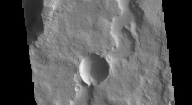 This image from NASAs Mars Odyssey shows an unnamed channel in northern Terra Cimmeria. Two impact craters occur along the length of the channel.