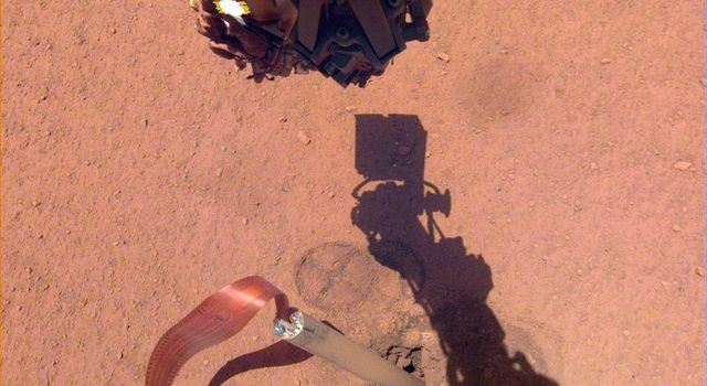 The shadow of NASA InSights robotic arm moves over its heat probe on Nov. 3, 2019, the 333rd Martian day, or sol, of the mission.