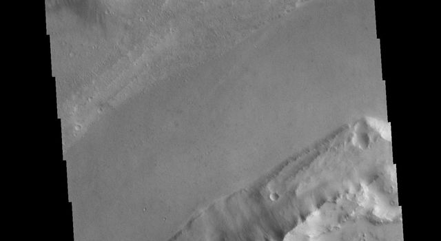 This image from NASAs Mars Odyssey shows the region where the northward flow of Kasei Valles turns to the east having split into two large channels.