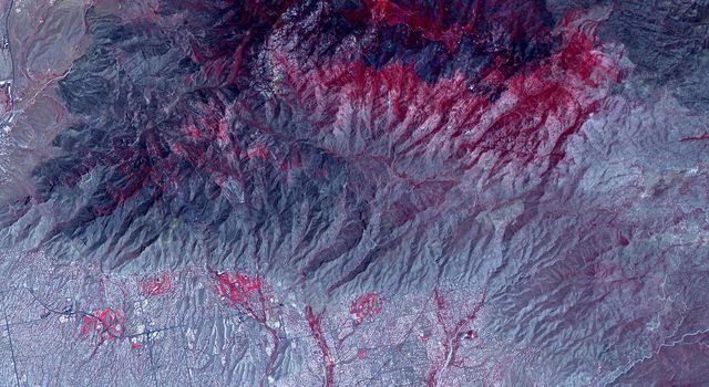 NASAs ASTER instrument imaged areas burned by the Bighorn Fire north of Tucson, Arizona, on June 29. Vegetation is shown in red and burned areas are shown in dark gray.