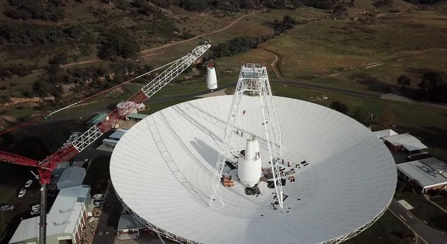 In a delicate operation, a 400-ton crane lifts the new X-band cone into the 70-meter (230-feet) Deep Space Station 43 dish located in Canberra, Australia.