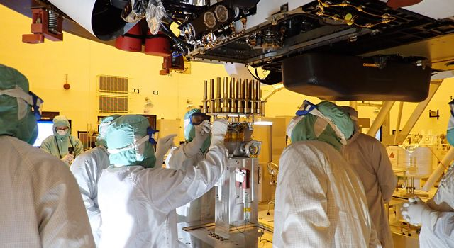Engineers and technicians working on the Mars 2020 Perseverance team insert 39 sample tubes into the belly of the rover.