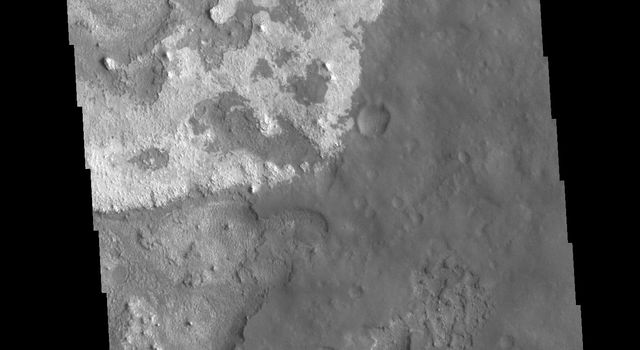 This image from NASAs Mars Odyssey shows layering of surface materials in Meridiani Planum.