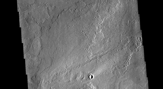 This image from NASAs Mars Odyssey shows part of the extensive volcanic flows in the Tharsis region.