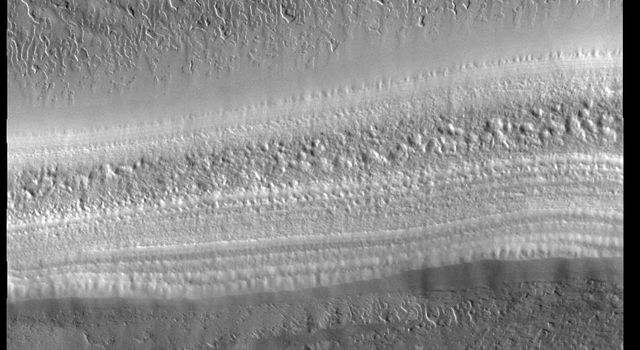This image from NASAs Mars Odyssey shows the South Polar Cap. A trough crosses the center of the image, showing the layered nature of the cap ice.