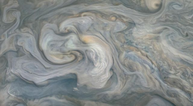 In the center of this JunoCam image, small, bright pop-up clouds seen rise above the surrounding features. Clouds like these are thought to be the tops of violent thunderstorms responsible for shallow lighting.