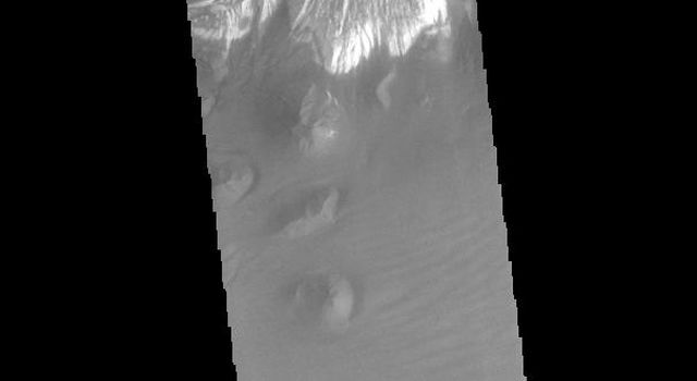 This image from NASAs Mars Odyssey shows part of the floor of Ganges Chasma. Deposits of fine surface materials and bright layered deposits are visible in this image.