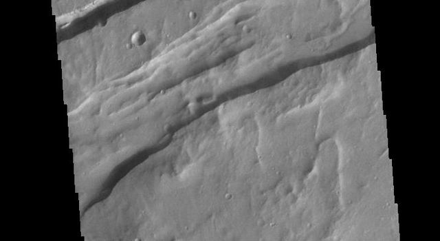 This image from NASAs Mars Odyssey shows linear depressions, part of Sirenum Fossae.